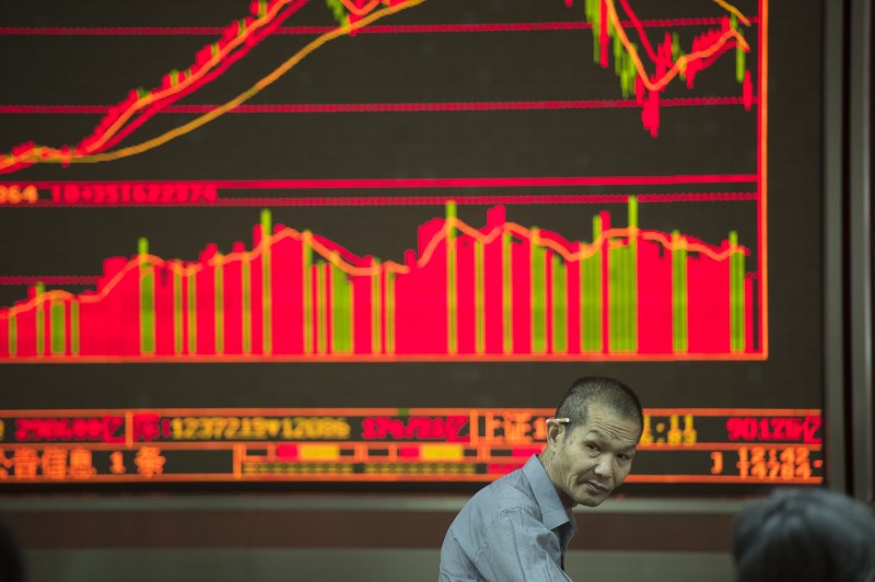 An investor looks at screens showing stock market movements at a securities company in Beijing on July 28, 2015. Chinese shares sank on July 28, a day after Shanghai's steepest one-day slide in eight years, defying renewed government vows of support that analysts warned were not enough to soothe nervous investors.       AFP PHOTO / FRED DUFOUR        (Photo credit should read FRED DUFOUR/AFP/Getty Images)