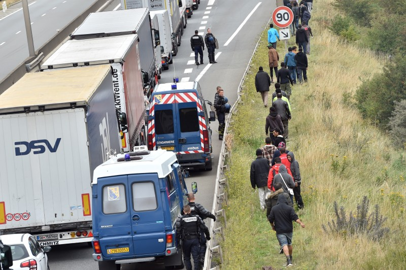 "French riot police stand on the side of the road to prevent migrants from approaching lorries on the road leading to the ferry port in Calais, northern France, on August 5, 2015. Britain and France were to announce a new ""command and control centre"" on August 20 for tackling smuggling gangs in Calais, where thousands of migrants desperate to cross the Channel are living in slum-like conditions.  AFP** PHOTO / PHILIPPE HUGUEN        (Photo credit should read PHILIPPE HUGUEN/AFP/Getty Images)"