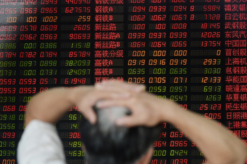 An investor gestures as he checks share prices at a securities firm in Shanghai on August 26, 2015. Shanghai stocks closed down 1.27 percent in volatile trading on August 26, extending days of falls despite a central bank interest rate cut aimed at boosting the flagging economy and slumping shares, dealers said.     CHINA OUT    AFP PHOTO        (Photo credit should read STR/AFP/Getty Images)