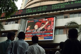 Indian pedestrians watch as a digital broadcast presents the rolling share price information and national election results news coverage on the facade of the Bombay Stock Exchange (BSE) building in Mumbai on May 16, 2014.   India's stock market jumped more than six percent to a record high of 25,000 points as business-friendly opposition leader Narendra Modi looked set for a landslide victory in national elections.  AFP PHOTO/ PUNIT PARANJPE        (Photo credit should read PUNIT PARANJPE/AFP/Getty Images)