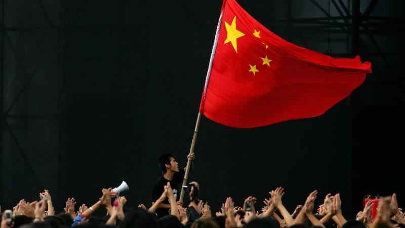 BEIJING - OCTOBER 02:  A Chinese teenager waves a national flag during a rock-and-roll festival to mark  Chinese National Day on October 2, 2005 in Beijing, China. Various activities are being held in China to mark the National Day.  (Photo by Guang Niu/Getty Images)