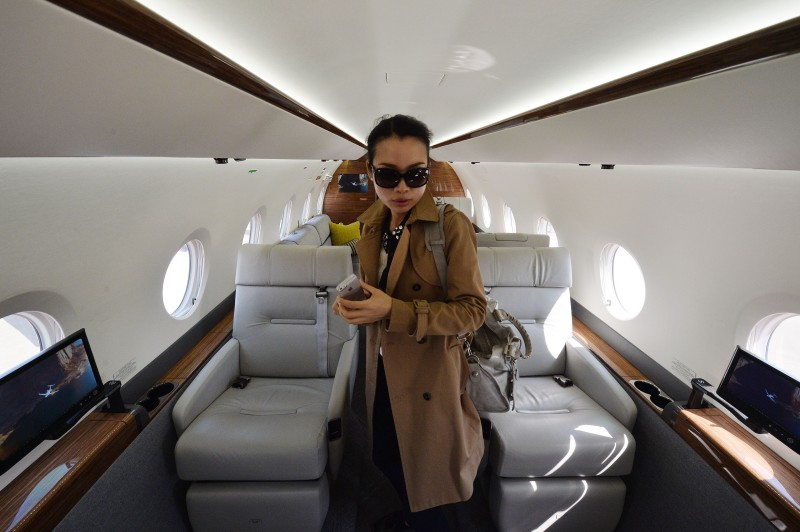 A Chinese woman looks at the interior of a Gulfstream G150 luxury business jet during the Asian Business Aviation Conference & Exhibition (ABACE2014) at the Shanghai Hongqiao airport on April 15, 2014.  Private plane ownership in China is still miniscule compared to countries like the US. State media reported only 150 such aircraft registered in 2011, despite an estimated one million millionaires as a result of the nation's economic boom.       AFP PHOTO/Mark RALSTON        (Photo credit should read MARK RALSTON/AFP/Getty Images)