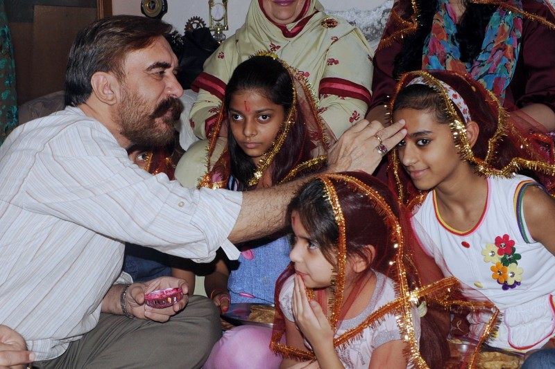 Pakistani member of the United Nations Human Rights Council and former human rights minister of Pakistan, Ansar Burney (L) places a tilak on the forehead of a young girl during the Kanjak Pooja on the last day of Navratri in Amritsar on October 22, 2012.  Held at the end of the Navratri festival, Dussehra symbolises the victory of good over evil in Hindu mythology. AFP PHOTO/ NARINDER NANU        (Photo credit should read NARINDER NANU/AFP/Getty Images)