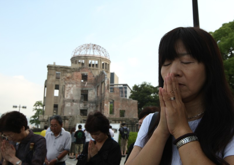 HIROSHIMA, JAPAN - AUGUST 06:  Japanese people pray for atomic bomb victims in front of a  Atomic Bomb Dome at the Hiroshima Peace Memorial Park on the day of the 68th anniversary of the atomic bombing of Hiroshima on August 6, 2013 in Hiroshima, Japan. Japan marks the 68th anniversary of the first atomic bomb that was dropped on Hiroshima by the United States on August 6, 1945, killing an estimated 70,000 people instantly with many thousands more dying over the following years from the effects of radiation. Three days later another atomic bomb was dropped on Nagasaki, ending World War II.  (Photo by Buddhika Weerasinghe/Getty Images)