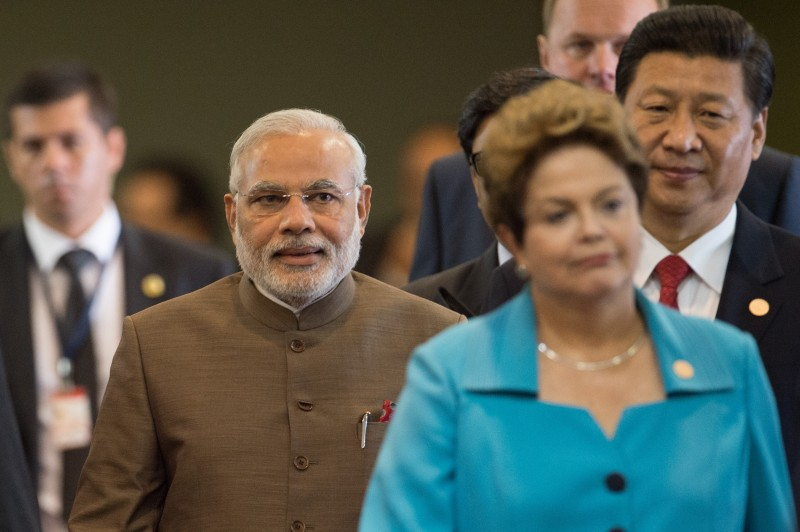 Indian Prime Minister Narendra Modi (L) walks next to Brazilian President Dilma Rousseff (C) and Chinese President Xi Jinping during the 6th BRICS Summit in Fortaleza, Brazil, on July 15, 2014.  - Leaders of the BRICS group of emerging powers huddled Tuesday in Brazil to launch a new development bank and a reserve fund seen as counterweights to Western-led financial institutions. AFP PHOTO / YASUYOSHI CHIBA        (Photo credit should read YASUYOSHI CHIBA/AFP/Getty Images)