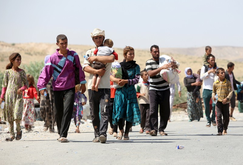 Displaced Iraqis from the Yazidi community carry their children as they cross the Iraqi-Syrian border at the Fishkhabur crossing, in northern Iraq, on August 11, 2014. At least 20,000 civilians, most of whom are from the Yazidi community, who had been besieged by jihadists on a mountain in northern Iraq have safely escaped to Syria and been escorted by Kurdish forces back into Iraq, officials said. The breakthrough coincided with US air raids on Islamic State fighters in the Sinjar area of northwestern Iraq on August 9, and Kurdish forces from Iraq, Syria and Turkey working together to break the siege of Mount Sinjar and rescue the displaced. AFP PHOTO/AHMAD AL-RUBAYE        (Photo credit should read AHMAD AL-RUBAYE/AFP/Getty Images)