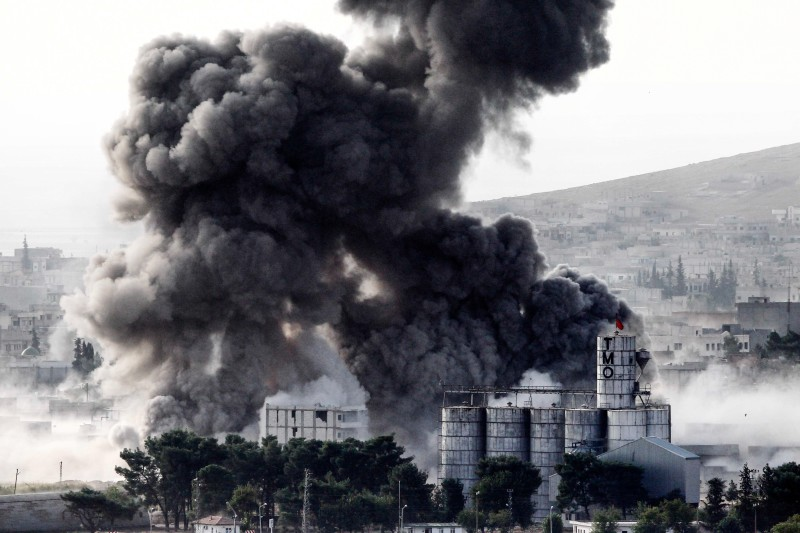 SANLIURFA, TURKEY -  OCTOBER 13: (TURKEY OUT) Heavy smoke rises following an airstrike by the US-led coalition aircraft in Kobani, Syria, during fighting between Syrian Kurds and the militants of Islamic State group, as seen from the outskirts of Suruc, on the Turkey-Syria border, October 13, 2014. The strategic border town of Kobani has been beseiged by Islamic State militants since mid-September forcing more than 200,000 people to flee into Turkey. (Photo by Gokhan Sahin/Getty Images)
