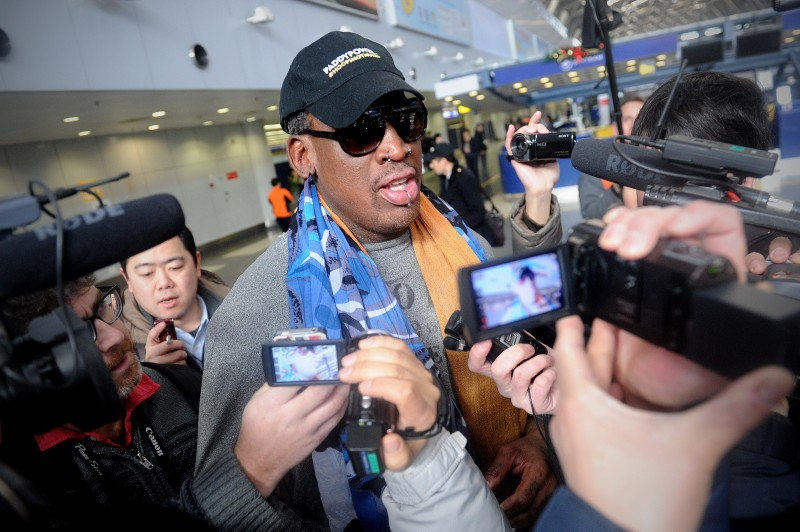 Former US NBA basketball player Dennis Rodman (C) speaks to members of the media as he makes his way through Beijing's international airport on December 19, 2013.  Rodman is on a visit to North Korea from December 19 to 23.    AFP PHOTO / WANG ZHAO        (Photo credit should read WANG ZHAO/AFP/Getty Images)
