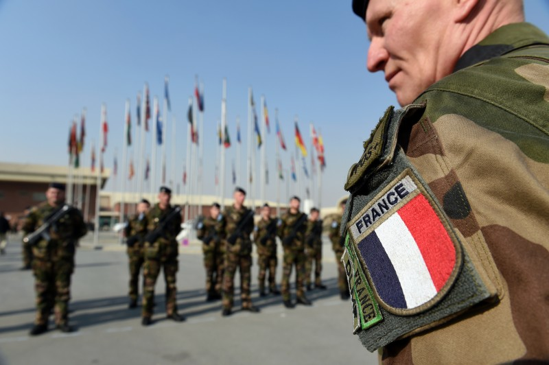 "The last French troops in Afghanistan stand during their end of NATO mission ceremony at Kabul International Airport (KAIA) in Kabul on December 31, 2014. The last French troops in Afghanistan held a ceremony in Kabul on December 31, to mark the end of their deployment after NATO combat operations closed down and as a new ""train and support"" mission takes over. About 150 French soldiers who had been helping run the military airport handed over responsibility to a Turkish unit which will operate under the new NATO mission. AFP PHOTO / SHAH Marai        (Photo credit should read SHAH MARAI/AFP/Getty Images)"