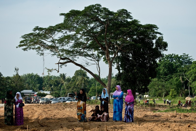 Local Malaysian women watch preparations for the re-burial of remains believed to be those of ethnic Rohingya found at human-trafficking camps in the country's north, at Kampung Tualang some 16kms east of Alor Setar on June 22, 2015. Malaysian authorities on June 22 held a sombre mass funeral for 21 suspected ethnic Rohingya found in human-trafficking graves last month, with fellow Muslims praying for the unidentified victims to find a place in heaven. AFP PHOTO / MANAN VATSYAYANA        (Photo credit should read MANAN VATSYAYANA/AFP/Getty Images)