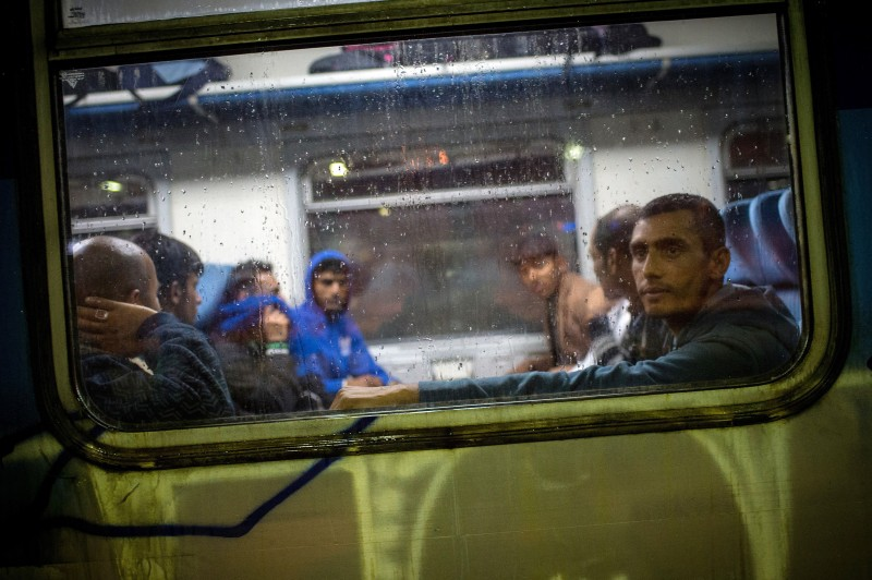 A group of migrants peer out from the carriage of a train bound for the Hungarian border at the main railway station in Belgrade on June 26, 2015. Four central European countries, Czech Republic, Hungary, Poland and Slovakia on June 25 called on the European Union to let member states decide for themselves how many migrants they will accept, instead of setting quotas. The number of immigrants entering Hungary has risen from 2, 000 in 2012 to 54, 000 this year so far. Hungary, which has seen 60,000 migrants crossing its border this year, said it would build a four-metre (13-foot) fence on its southern border with Serbia through which most migrants come into the country.  AFP PHOTO / ANDREJ ISAKOVIC        (Photo credit should read ANDREJ ISAKOVIC/AFP/Getty Images)