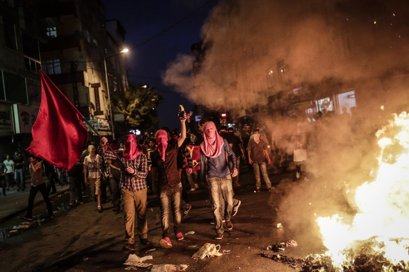 Left wing protesters shout slogans and hold red flag during a demonstration denouncing a police operation against Kurdish militants, on July 24, 2015 at Gazi district in Istanbul. Turkey on July 24 vowed to press on with operations against Islamic State (IS) in Syria and other militant groups, after its war planes bombed the jihadists' positions for the first time. Following the pre-dawn air raids on the IS targets in Syria, Turkish police arrested almost 300 suspected members of IS and pro-Kurdish militant groups nationwide, in one of Turkey's biggest recent crackdowns on extremists. AFP PHOTO/AFP PHOTO/YASIN AKGUL        (Photo credit should read YASIN AKGUL/AFP/Getty Images)