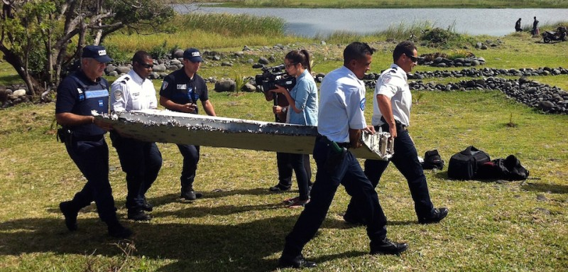 Police carry a piece of debris from an unidentified aircraft found in the coastal area of Saint-Andre de la Reunion, in the east of the French Indian Ocean island of La Reunion, on July 29, 2015.  The two-metre-long debris, which appears to be a piece of a wing, was found by employees of an association cleaning the area and handed over to the air transport brigade of the French gendarmerie (BGTA), who have opened an investigation. An air safety expert did not exclude it could be a part of the Malaysia Airlines flight MH370, which went missing in the Indian Ocean on March 8, 2014. AFP PHOTO / YANNICK PITOU        (Photo credit should read YANNICK PITOU/AFP/Getty Images)