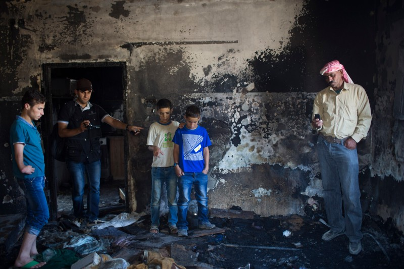 DUMA,WEST BANK - JULY 31:   Family members and relatives of 18 month old baby, Ali Saad-Dawabsheh, view the remains of their house after a fire which was suspected to have been set by Jewish extremists on July 31, 2015 in the Palestinian village of Duma, West Bank.  A house fire in the Palestinian village of Duma, West Bank, suspected to have been set by Jewish extremists, killed an 18-month-old Palestinian child, injured both parents and a four year old brother. (Photo by Oren Ziv/Getty Images)