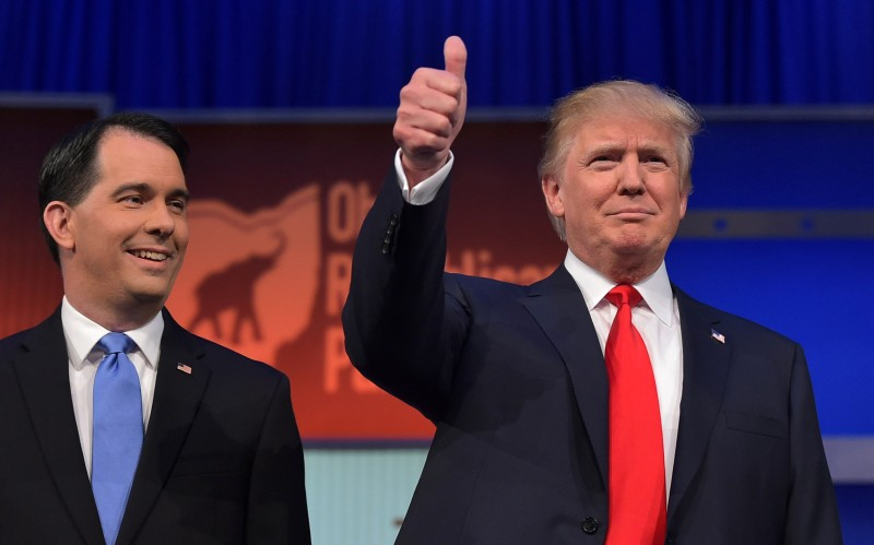 Real estate tycoon Donald Trump (R) and Wisconsin Gov. Scott Walker (L) arrive on stage for the Republican presidential primary debate on August 6, 2015 at the Quicken Loans Arena in Cleveland, Ohio. AFP PHOTO / MANDEL NGAN        (Photo credit should read MANDEL NGAN/AFP/Getty Images)