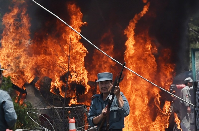 "An Afghan policeman stands guard as smoke and flames rise from the site of a huge blast struck near the entrance of Kabul's international airport, in Kabul on August 10, 2015. A huge blast struck near the entrance of Kabul's international airport on August 10 during the peak lunchtime period, officials said, warning that heavy casualties were expected. ""The explosion occurred at the first check point of Kabul airport,"" said deputy Kabul police chief Sayed Gul Agha Rouhani. AFP PHOTO / SHAH Marai        (Photo credit should read SHAH MARAI/AFP/Getty Images)"