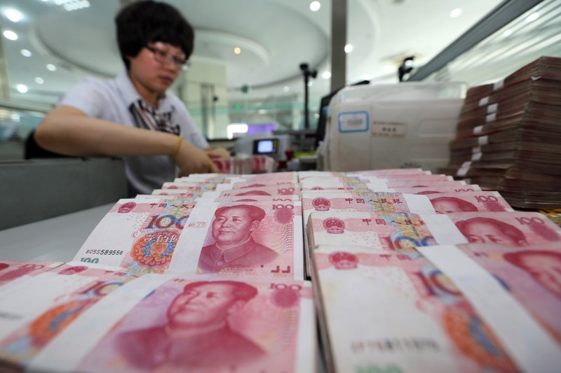 A teller counts yuan banknotes in a bank in Lianyungang, east China's Jiangsu province on August 11, 2015. China's central bank on August 11 devalued its yuan currency by nearly two percent against the US dollar, as authorities seek to push market reforms and bolster the world's second-largest economy. CHINA OUT   AFP PHOTO        (Photo credit should read STR/AFP/Getty Images)