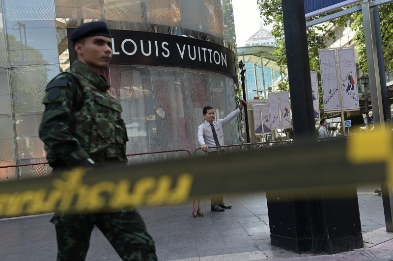 An investigator stands by the shattered window of a luxury shop at the cordoned-off site of a bomb blast at the popular Erawan shrine in the heart of Bangkok's tourist and commercial centre on August 18, 2015.  The death toll from a bomb blast in the Thai capital rose to 21 on August 18 with 123 wounded, police said, with seven tourists from China, Hong Kong, Malaysia and Singapore among those killed in the attack.   AFP PHOTO / Christophe ARCHAMBAULT        (Photo credit should read CHRISTOPHE ARCHAMBAULT/AFP/Getty Images)