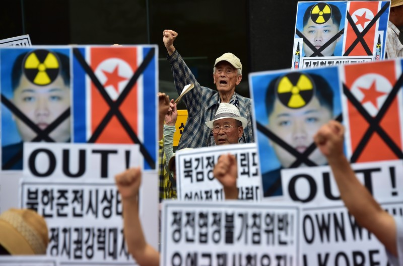 South Korean conservative activists hold placards showing portraits of North Korean leader Kim Jong-Un during a rally denouncing North Korea's rocket firing, in Seoul on August 21, 2015. North Korean leader Kim Jong-Un ordered his frontline troops onto a war-footing from August 21, as military tensions with South Korea soared following a rare exchange of artillery shells across their heavily fortified border.    AFP PHOTO / JUNG YEON-JE        (Photo credit should read JUNG YEON-JE/AFP/Getty Images)