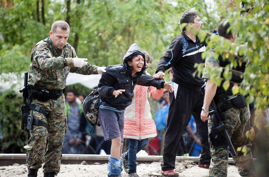 A member of the Macedonian police force and a migrant hold an injured boy during a clash between Macedonian police forces and migrant trying to cross an illegal crossing point on the border between Greece and Macedonia near the town of Gevgelija on August 22, 2015. Hundreds of mostly Syrian refugees forced their way over the Macedonian border today as police hurled stun grenades in a failed bid to stop them breaking through, an AFP reporter said. AFP  PHOTO / ROBERT ATANASOVSKI        (Photo credit should read ROBERT ATANASOVSKI/AFP/Getty Images)
