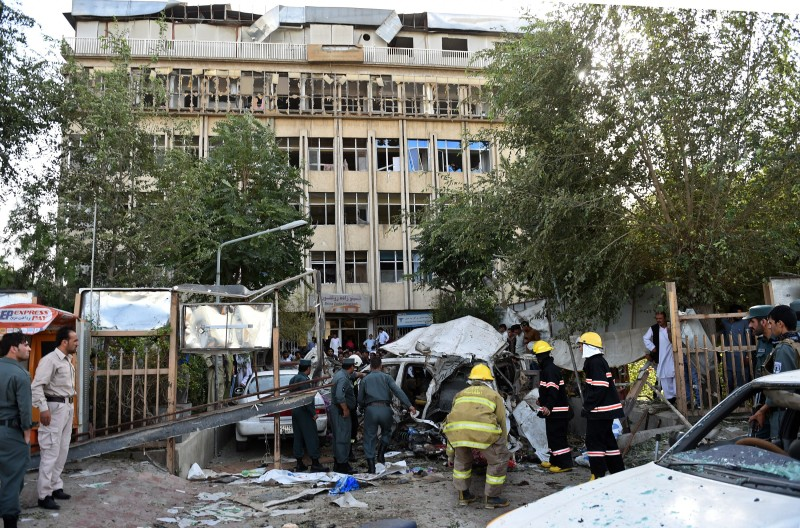 Afghan police and security forces inspect the site of a car bomb in Kabul on August 22, 2015. A suicide car bomb apparently targeting a foreign forces convoy killed three people in downtown Kabul on August 22, officials said, underlining the precarious security situation in the Afghan capital following a recent wave of fatal bombings. AFP PHOTO / WAKIL KOHSAR        (Photo credit should read WAKIL KOHSAR/AFP/Getty Images)