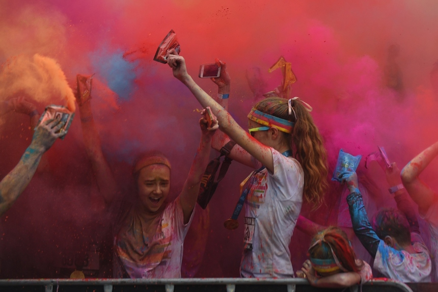 People participate in the annual Color Run after party in Centennial Park in Sydney on August 23, 2015. The Color Run is a 5km fun run started in the US in 2012 and is inspired by the traditional Hindu festival Holi, where people throw natural coloured powders as the seasons change from winter to spring. AFP PHOTO / Peter PARKS        (Photo credit should read PETER PARKS/AFP/Getty Images)
