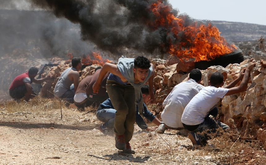 Palestinians take cover behind a low wall during clashes between Palestinian farmers and Israeli security forces and Israeli settlers from the nearby Esh Kodesh outpost settlement on August 22, 2015 in the West Bank village of Qusra. Qusra is just a few kilometres (miles) north of Esh Kodesh, a village and an Israeli settlement outpost, and is the scene of frequent clashes between settlers and Palestinians.  AFP PHOTO / JAAFAR ASHTIYEH        (Photo credit should read JAAFAR ASHTIYEH/AFP/Getty Images)