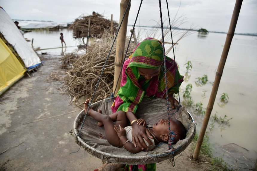 A mother comforts her son at a temporary shelter in the flood affected Morisutitop village, in the Morigaon district of north eastern Assam state on August 23, 2015. Seven people have died and over 650,000 people have been affected by floods in Assam. AFP PHOTO/ Biju BORO          (Photo credit should read BIJU BORO/AFP/Getty Images)