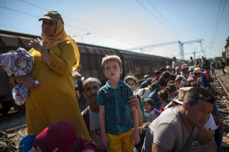 Migrants wait on a platform at the train station in the town of Gevgelija, on the Macedonian-Greek border, to receive permission from police officers before boarding trains to Serbia on August 23, 2015. More than 1,500 mostly Syrian refugees, trapped in a no-man's land for three days, entered Macedonia from Greece, after police allowed them to pass despite earlier trying to hold back the crowd using stun grenades. AFP PHOTO / ROBERT ATANASOVSKI        (Photo credit should read ROBERT ATANASOVSKI/AFP/Getty Images)