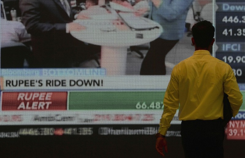 An Indian stockbroker watches currency rates on a screen during a trading session at the Bombay Stock Exchange in Mumbai on August 24, 2015. The plummenting Chinese market on August 24 led a slump across Asian equities, as Beijing's latest intervention failed to restore confidence.   AFP PHOTO/ INDRANIL MUKHERJEE        (Photo credit should read INDRANIL MUKHERJEE/AFP/Getty Images)