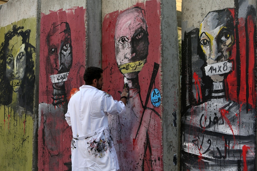 A Lebanese protester draws graffiti on concrete blast walls, recently erected by security forces, on the road leading to the governmental palace on August 24, 2015 in the capital Beirut. Activists in Lebanon vowed to press ahead with protests over a trash crisis that have become an outlet for deep-rooted, broad-based frustration over political stagnation, corruption, and crumbling infrastructure. AFP PHOTO / STR        (Photo credit should read -/AFP/Getty Images)