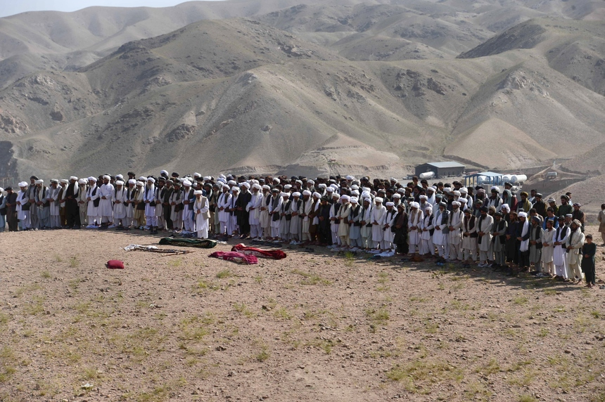 Afghan mourners offer funeral prayers during a ceremony after a series of explosions at a gas storage facility on the edge of the western city of Herat on August 25, 2015.  At least 11 people including several children were killed in a series of explosions at a gas storage facility on the edge of the western city of Herat, officials said on August 25. The explosions triggered an inferno which spread to a nearby camp for internally displaced people where most of the deaths occurred.   AFP PHOTO / Aref Karimi        (Photo credit should read Aref Karimi/AFP/Getty Images)