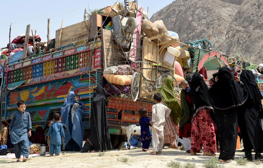 """Afghan refugee women and children gather beside loaded trucks at the United Nations High Commissioner for Refugees (UNHCR) repatriation centre on the outskirts of Quetta on August 26, 2015, as they prepare to return to their home country after fleeing civil war and Taliban rule.  Pakistan has the world's second-largest refugee population, 1.5 million, most of them Afghans living for years in poor conditions in camps in the restive northwest. The number of Afghans crossing the border back to their homeland Afghanistan in the first four months of this year fleeing """"pressure"""" from Pakistani officials was nine times higher than the same period last year, according to the International Organisation for Migration. AFP PHOTO / BANARAS KHAN        (Photo credit should read BANARAS KHAN/AFP/Getty Images)"""