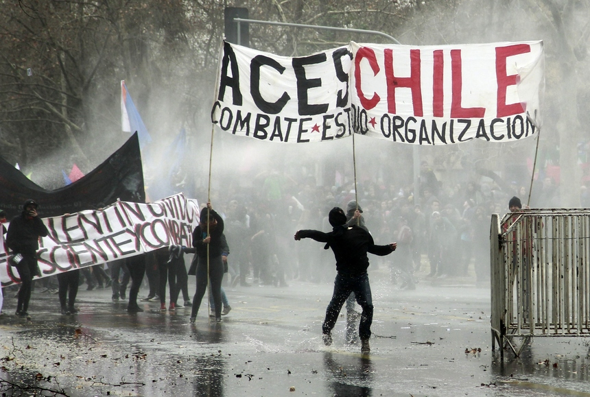 Students clash with the riot police during a demonstration against an education reform plan pushed by the government of President Michelle Bachelet, in Santiago on August 27, 2015. Critics say the reforms fall short of overhauling a highly unequal education system inherited from the 1973-1990 dictatorship of late ruler Augusto Pinochet.   AFP PHOTO / CLAUDIO REYES        (Photo credit should read Claudio Reyes/AFP/Getty Images)