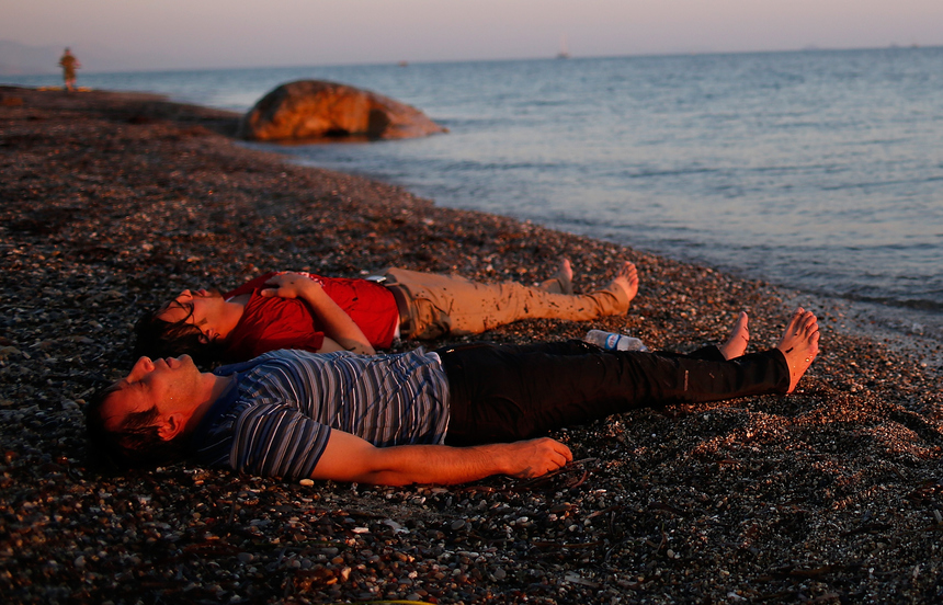 KOS, GREECE - AUGUST 28:  Overcome with exhaustion after swimming the final 50 yards of their journey, two migrants from Syria lay on the beach on the island of Kos after crossing a three mile stretch of the Aegean Sea in a small boat from Turkey August 28, 2015 in Kos, Greece. Migrants from the Middle East and North Africa continue to flood into Europe at a rate that marks the largest migration since World War II.  (Photo by Win McNamee/Getty Images)