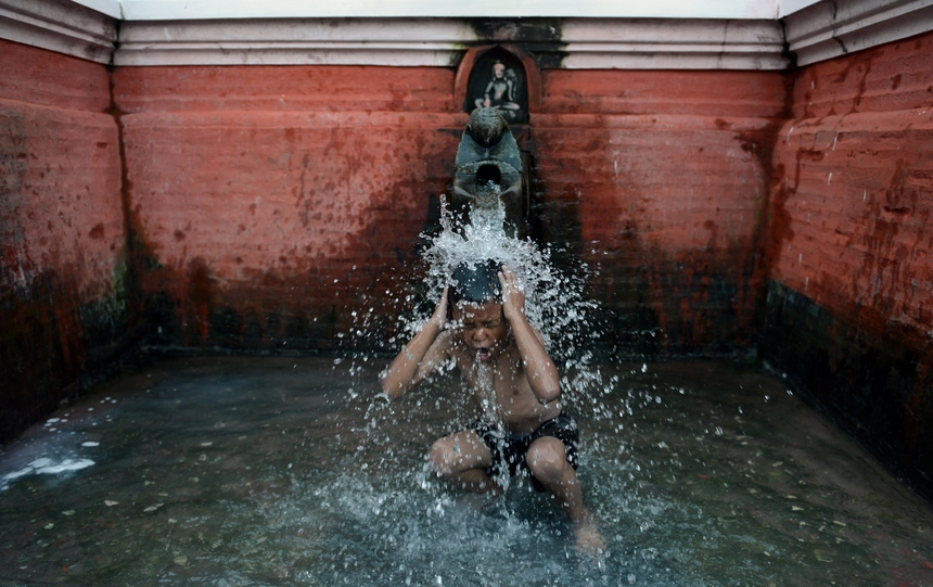 A Nepalese boy bathes under a stone spout near the Patan Durbar Square in Lalitpur, some five kms south-east of Kathmandu on August 28, 2015. Patan Durbar Square, a UNESCO World Heritage Site, is best known for its rich cultural heritage, particularly its tradition of arts and crafts. AFP PHOTO/ Prakash MATHEMA        (Photo credit should read PRAKASH MATHEMA/AFP/Getty Images)