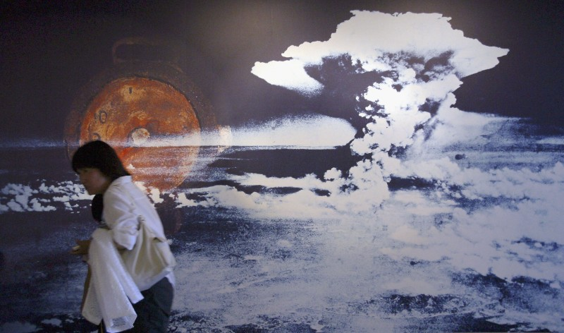 HIROSHIMA, JAPAN - AUGUST 5:  A visitor passes by a wall displaying a picture of the mushroom cloud pictured when the atomic bomb was dropped on August 5, 2004 in Hiroshima, Japan. Tomorrow Hiroshima will mark the 59th anniversary of the dropping of the first atomic bomb in Hiroshima at the Hiroshima Peace Memorial Park. (Photo by Junko Kimura/Getty Images)