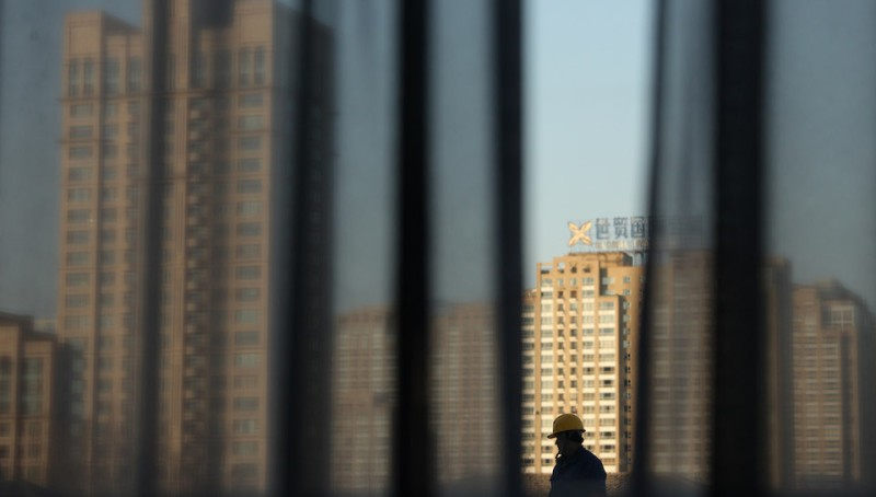 A construction worker walks before buildings of the Beijing skyline on December 21, 2011. Home prices in most major Chinese cities fell in November from the previous month, official data showed December 18, as government efforts to cool the red-hot property market prove effective. AFP PHOTO / ED JONES (Photo credit should read Ed Jones/AFP/Getty Images)