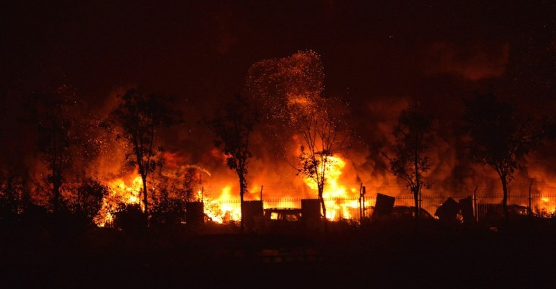 Flames and smoke rise from the site of a series of explosions in Tianjin early on August 13, 2015. A series of massive explosions at a warehouse in the northern Chinese port city of Tianjin killed 17 people, state media reported August 13, as witnesses described a fireball from the blasts ripping through the night sky. CHINA OUT AFP PHOTO        (Photo credit should read STR/AFP/Getty Images)