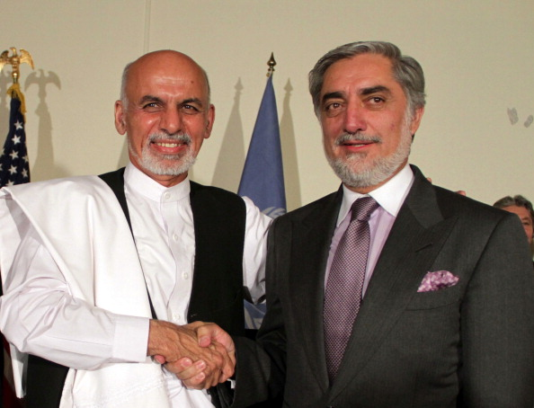 KABUL, AFGHANISTAN - JULY 12: Afghanistan's presidential candidates Ashraf Ghani Ahmadzai (L) and Abdullah Abdullah (R) shake hand at a joint press conference followed their meeting to put forward a power-sharing deal to resolve the dispute over preliminary election results in Kabul, July 12, 2014. Both candidates have committed to abide by the result of the most thorough audit. Afghanistan would audit all eight million votes cast in a runoff presidential election last month as part of a deal to end a tense power struggle between the two candidates. (Photo by Haroon Sabawoon/Anadolu Agency/Getty Images)