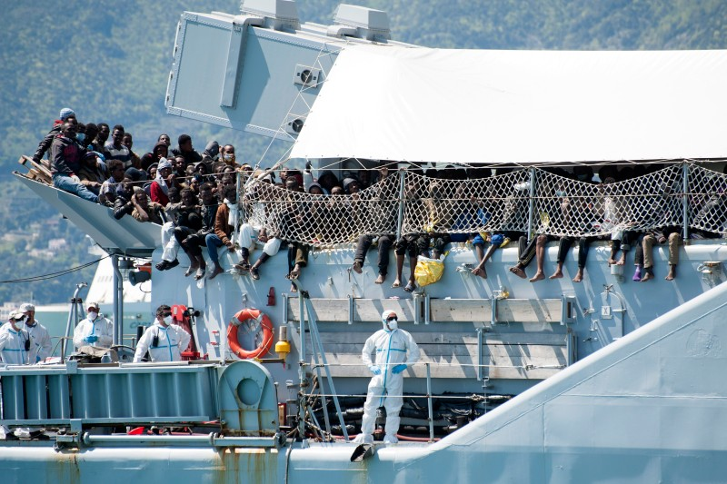 SALERNO, ITALY - APRIL 22:  Migrants wait to disembark from the Italian Navy vessel 'Chimera' in the harbor of Salerno on April 22, 2015 in Salerno, Italy. The Italian navy brought 545 migrants to Salerno, on the mainland of Italy, in a bid to ease the pressure on overcrowded centres receiving migrants in ports in Sicily. Migrants continue to arrive on the island of Lampedusa from North Africa, taking advantage of calm seas. Hundreds of migrants are believed to have perished over the past week as they attempted to cross the Mediterranean from Libya to Italy in order to seek refuge. (Photo by Ivan Romano/Getty Images)
