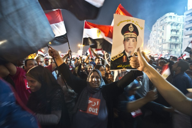 People celebrate at Tahrir Square with a portrait of Army chief Abdel Fattah al-Sisi after a broadcast confirming that the army will temporarily be taking over from the country's first democratically elected president Mohamed Morsi on July 3, 2013 in Cairo. In their tens of thousands, they cheered, ignited firecrackers and honked horns as soon as the army announced Morsi's rule was over, ending Egypt's worst crisis since its 2011 revolt. AFP PHOTO / KHALED DESOUKI        (Photo credit should read KHALED DESOUKI/AFP/Getty Images)