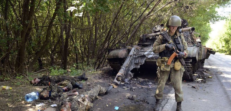 A pro-Russia militant stands guard next to a Ukrainian tank destroyed by separatists with the bodies of the crew members lying beside it in the eastern Ukrainian city of Donetsk on July 22, 2014. Terrified civilians fled as intense clashes on July 21 between Ukrainian government troops and pro-Russian rebels left at least four people dead on the outskirts of the insurgent bastion of Donetsk. A military spokesman said yesterday government troops were battling back control of the districts around the airport and had broken through the rebel cordon to reach their comrades inside. AFP PHOTO/ ALEXANDER KHUDOTEPLY        (Photo credit should read Alexander KHUDOTEPLY/AFP/Getty Images)