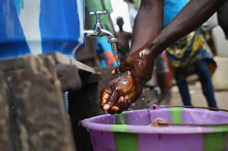 MONROVIA, LIBERIA - AUGUST 19:  A resident washes his hands in chlorinated water at a public bathroom in the West Point slum on August 19, 2014 in Monrovia, Liberia. An holding center in West Point for people suspected of having the Ebola virus was overrun and shut down by a crowd on August 16. The Ebola virus has killed more than 1,000 people in four African nations, more in Liberia than any other country.  (Photo by John Moore/Getty Images)