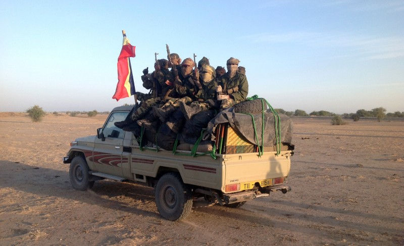 Soldiers of the Chadian hold a Chadian national flag as they patrol in armoured vehicles on January 21, 2015, at the border between Nigeria and Cameroon, some 40 km from Maltam, as part of a military contingent against the armed Islamist group Boko Haram. Chad, seen as having the most capable military in the region, sent on January 17-18, 2015 a convoy of troops and 400 military vehicles into neighbouring Cameroon to battle Boko Haram. AFP PHOTO / ALI KAYA        (Photo credit should read ALI KAYA/AFP/Getty Images)