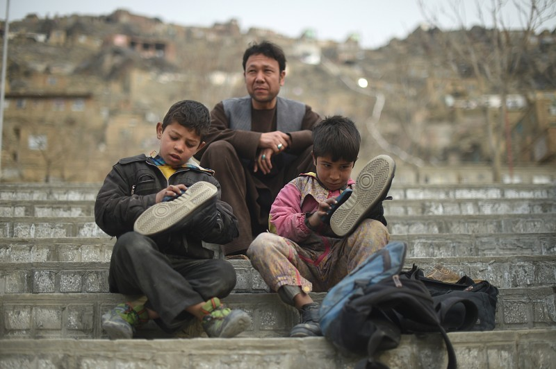 Afghan shoe-shine boy Sameiullah (R), 11, polishes a customer's shoes at the Karta-e-Sakhi cemetery in Kabul on February 10, 2015. Sameiullah, the second son of his eight-member family, is the sole bread-winner who polishes shoes of customers from dawn to dusk in western Kabul, making roughly 4 USD daily. Poverty and insecurity has forced thousands of children into child labour in Afghanistan. Children aged five to fifteen instead of attending schools work on the streets and are often the sole bread-winners of their families. AFP PHOTO / SHAH MARAI        (Photo credit should read SHAH MARAI/AFP/Getty Images)