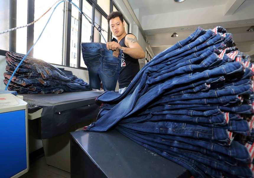 This picture taken on May 12, 2015 shows a Chinese worker making jeans at a clothing factory in Shishi, east China's Fujian province. Retail sales growth in China fell to 10.0 percent in April, missing expectations and the lowest for nine years, while industrial output in the world's second-largest economy rose 5.9 percent in the same month, the National Bureau of Statistics said, while fixed asset investment, a measure of government spending on infrastructure, expanded 12.0 percent in the first four months of the year.              AFP PHOTO   CHINA OUT        (Photo credit should read STR/AFP/Getty Images)