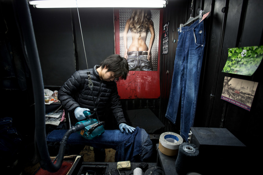"KURASHIKI, JAPAN - FEBRUARY 25: (EDITORS NOTE: Image contains nudity)  A worker shaves creases into a pair of jeans at the Bitou denim processing facility in Kojima district on February 25, 2014 in Kurashiki, Japan. Kojima is a small seaside district in the west of Japan and is known as ""Japan's Denim Mecca"" with many of the world's finest jean brands being crafted from some of the 200 factories and firms operating from the city. Kojima's manufacturers have won acclaim from apparel brands in Japan and overseas due to their high level of craftsmanship and unique techniques. With many companies using older machines or handmade techniques to insure outstanding quality. Along with the many manufacturers the city also has a "" Jean Street "" which is home to over 20 retail stores, selling high-end clothing and jeans attracting many tourists and designers.  (Photo by Chris McGrath/Getty Images)"