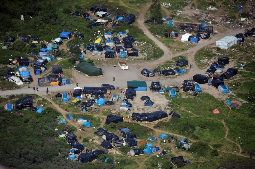 "An aerial picture taken on June 4, 2015 shows ""the jungle"", a makeshift tent village set up by illegal migrants in Calais, northern France. Around 2,500 migrants, mostly from Sudan, Eritrea and Syria, live in this camp, close to the Channel Tunnel, through which migrants seek to reach Britain. AFP PHOTO / FRANCOIS LO PRESTI        (Photo credit should read FRANCOIS LO PRESTI/AFP/Getty Images)"