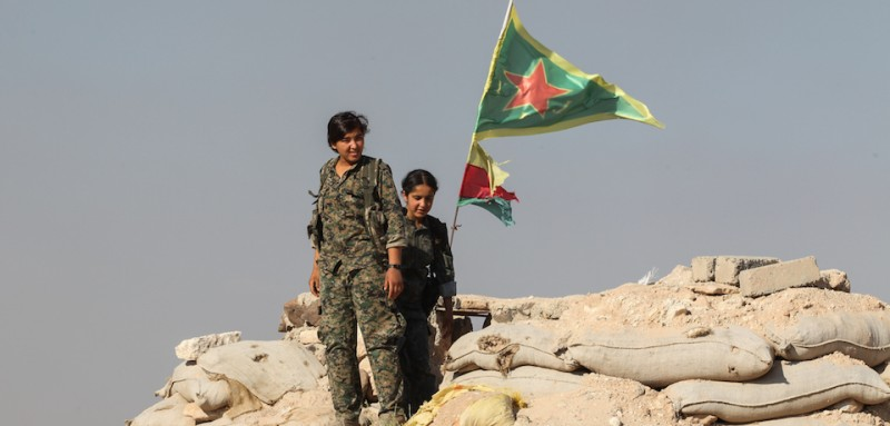 KOBANE, SYRIA - JUNE 20: (TURKEY OUT) A Kurdish People's Protection Units, or YPG women fighters pose as they stand near a check point in the outskirts of the destroyed Syrian town of Kobane, also known as Ain al-Arab, Syria. June 20, 2015. Kurdish fighters with the YPG took full control of Kobane and strategic city of Tal Abyad, dealing a major blow to the Islamic State group's ability to wage war in Syria. Mopping up operations have started to make the town safe for the return of residents from Turkey, after more than a year of Islamic State militants holding control of the town. (Photo by Ahmet Sik/Getty Images)